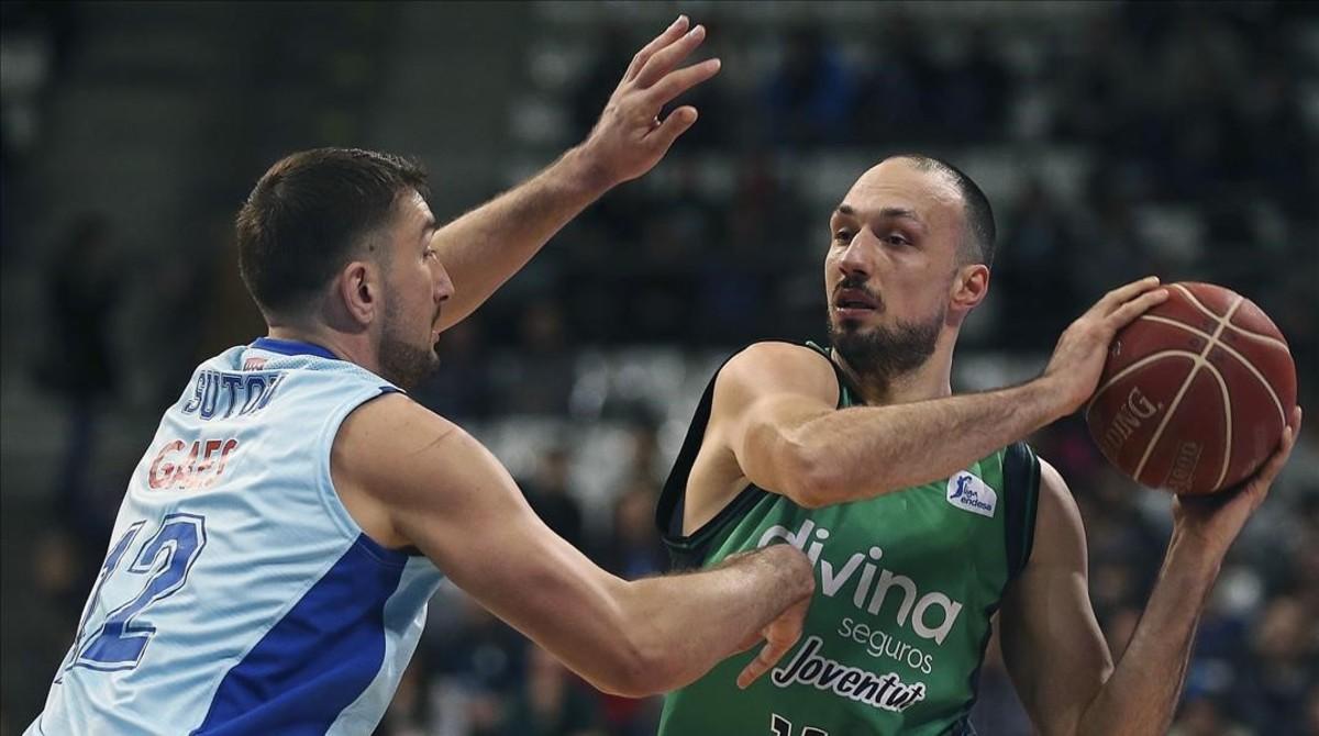 El ala-pívot serbio del Joventut Luka Bogdanovic busca el pase ante el croata del Estudiantes Goran Suton.
