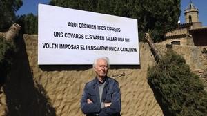 Albert Boadella posa frente a un cartel en el que denuncia los ataques que está sufriendo en su casa del Empordà.