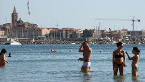 La playa de lAlguer, en la isla de Cerdeña, con el municipio medieval al fondo.