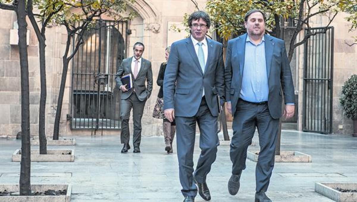 Carles Puigdemont y Oriol Junqueras caminan por el Pati dels Tarongers del Palau de la Generalitat, antes de una reunión de Govern.