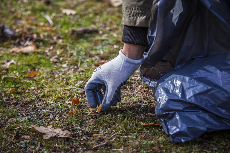 Proyecto Libera. Un voluntario recoge colillas en el campo.