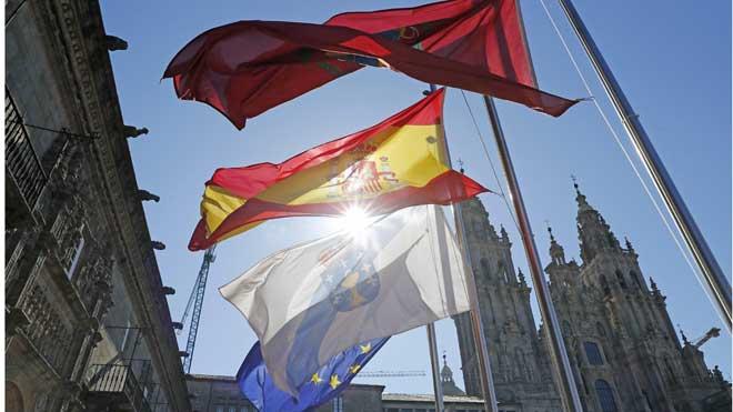 España comienza diez días de luto oficial por las víctimas del coronavirus. En la foto, banderas a media asta en la plaza del Obradoiro, en Santiago de Compostela. En el vídeo, imágenes de edificios oficiales en Madrid.