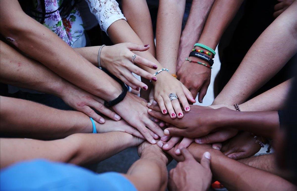 Un grupo de niños uniendo sus manos.