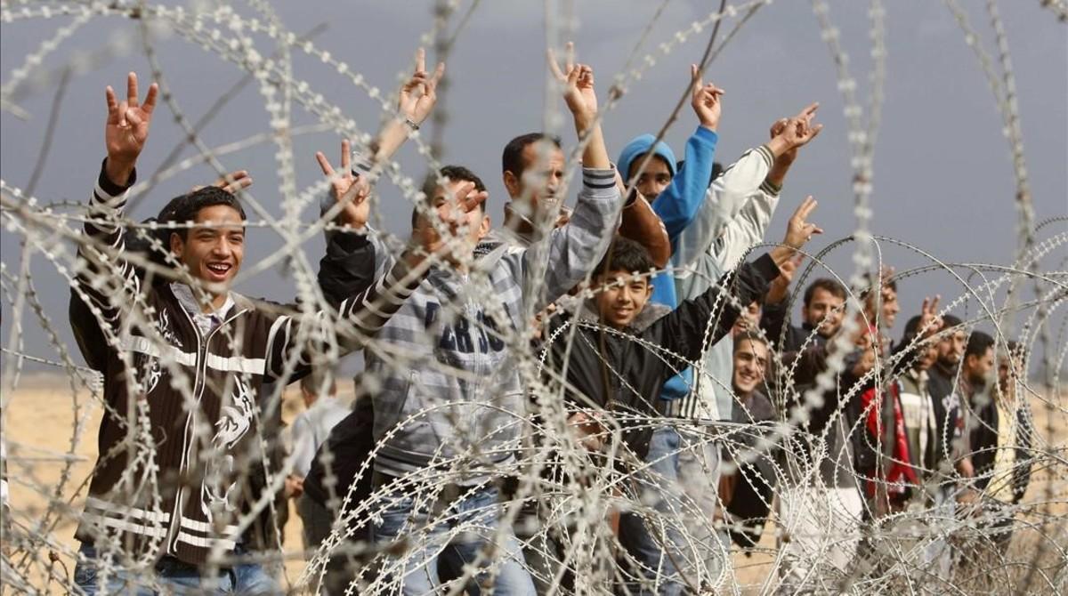 Un grupo de palestinos gesticulan a soldados israelís de guardia cerca de la valla entre Israel y la franja de Gaza, el 23 de noviembre del 2012.