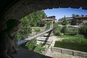 Un hombre observa el puente colgante de Rupit.
