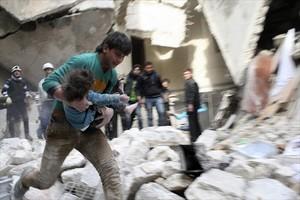 Un hombre traslada a una niña herida tras un bombardeo en Alepo.