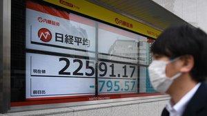 Un transeúnte pasa ante un marcador del índice Nikkei en Tokio.
