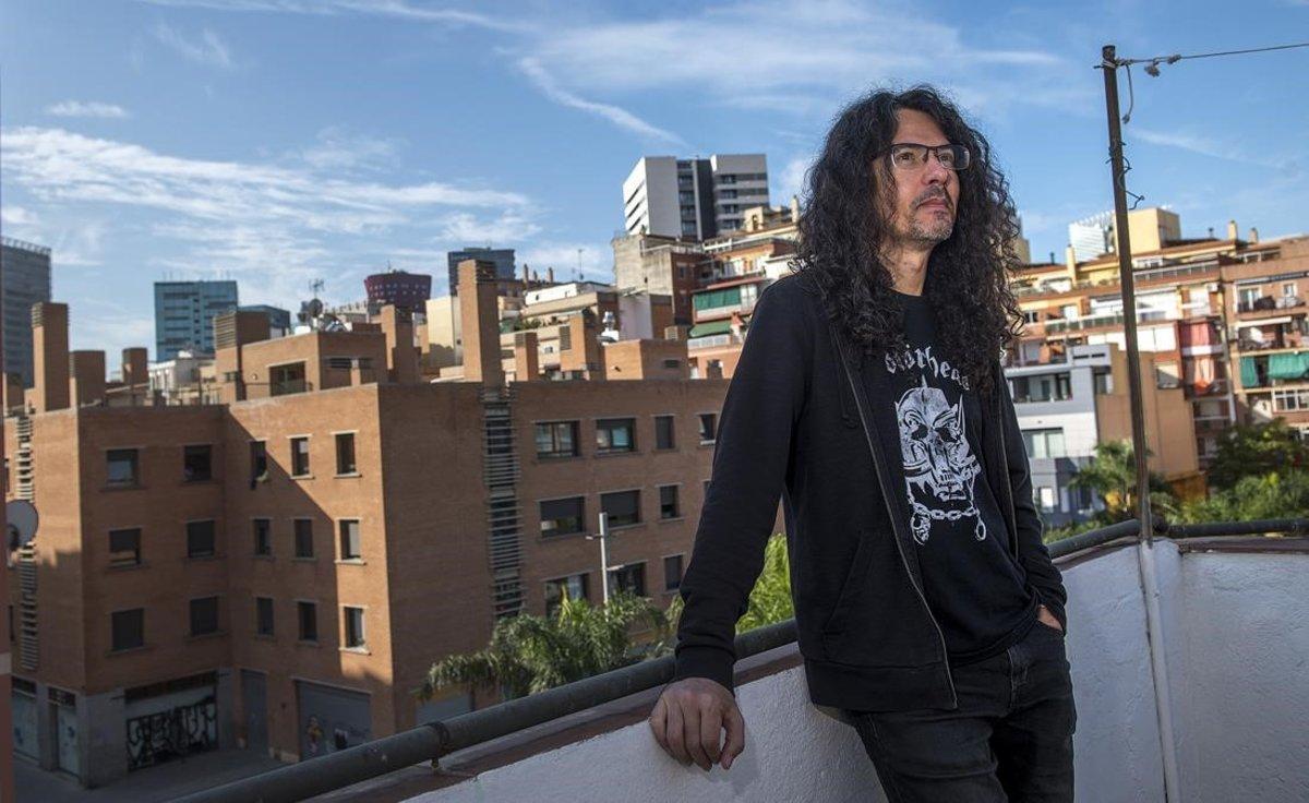 El dibujanteJaime Martín, fiel a Motörhead como demuestra su camiseta, rodeado de edificios del viejo y el nuevo L'Hospitalet, en la casa donde creció, la pasada semana.