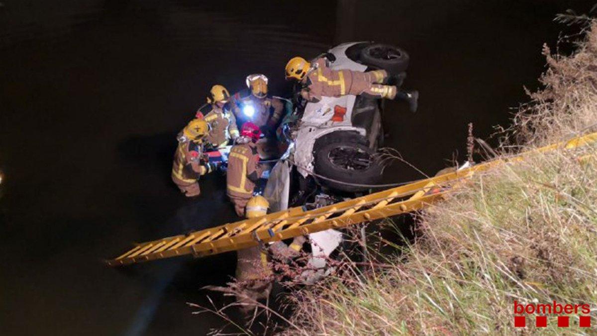 Los Bomberos retiran elcoche caído a un canal de El Prat.