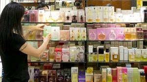Una dependienta ordena el expositor de perfumes y colonias en una tienda de Barcelona.