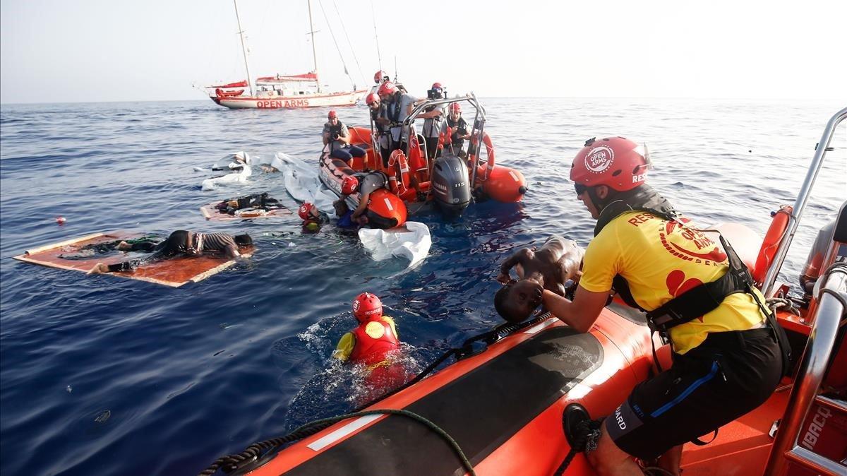 Un miembro de Proactiva Arms saca un cadáver del agua mientras sus compañeros rescatan a una mujer del agua