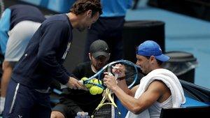 Nadal pone cinta en su raqueta ante la presencia de su entrenador, Carlos Moya.