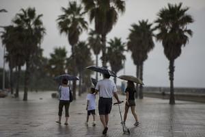 Una familia se protege con paraguas de la lluvia en la playa del Fòrum, en una imagen de archivo.
