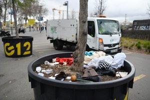 Operarios de limpieza retiran los restos del 'mercado de la miseria' que diariamente se instala junto al centro comercial Glòries.