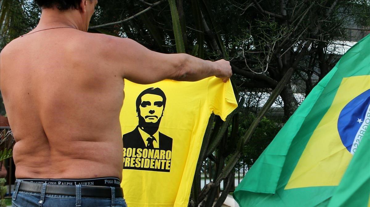 Un partidario de Bolsonaro enseña una camiseta con su cara en Rio de Janeiro
