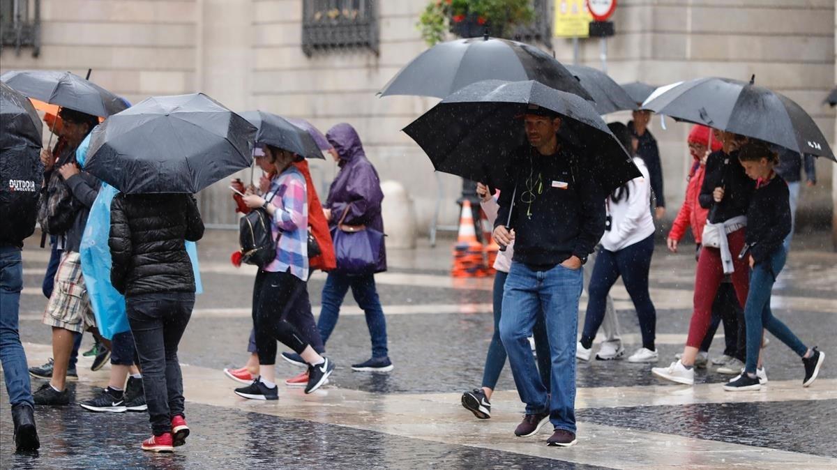 Peatones con paraguas en la plaça de Sant Jaume, hoy martes.