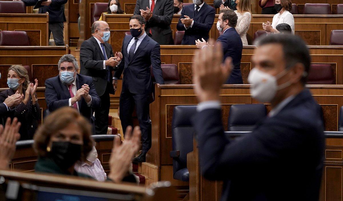 El presidente del Gobierno, Pedro Sánchez, aplaude el resultado de la moción de censura perdida por el líder de Vox, Santiago Abascal, al fondo, este 22 de octubre en el Congreso.