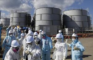 Periodistas protegidos con trajes de protección en una visita a Fukushima.