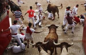 Varios mozos pasan apuros ante los toros de la ganaderia de Yeltesen el tramo del Callejón durante el cuarto encierro de San Fermín del 2016.