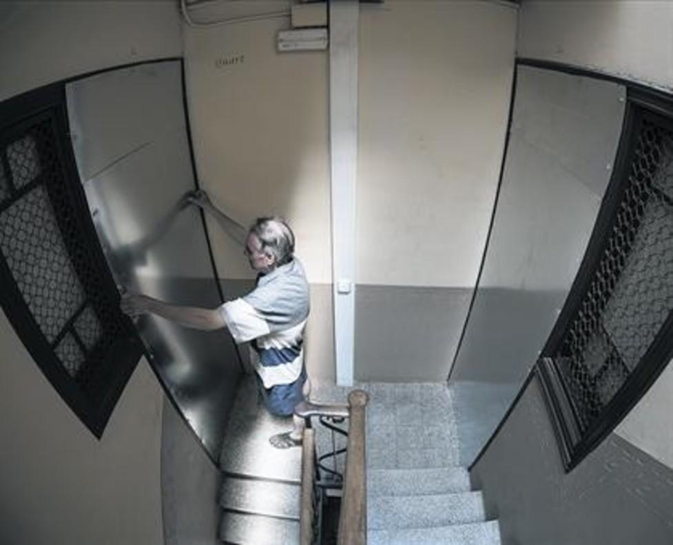 Un operario chapa con planchas de hierro las puertas de pisos vacíos de Entença 151.