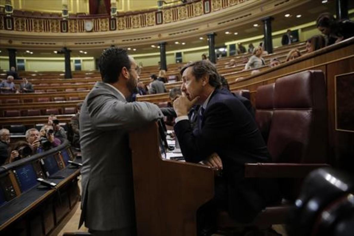 El socialista Antonio Hernando (izquierda) y el popular Rafael Hernando conversan en el hemiciclo del Congreso.
