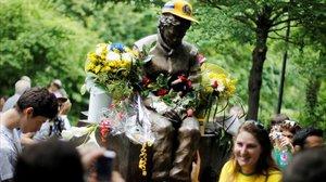 Una aficionada brasileña posa junto a la estatua que recuerda a Ayrton Senna en Imola.