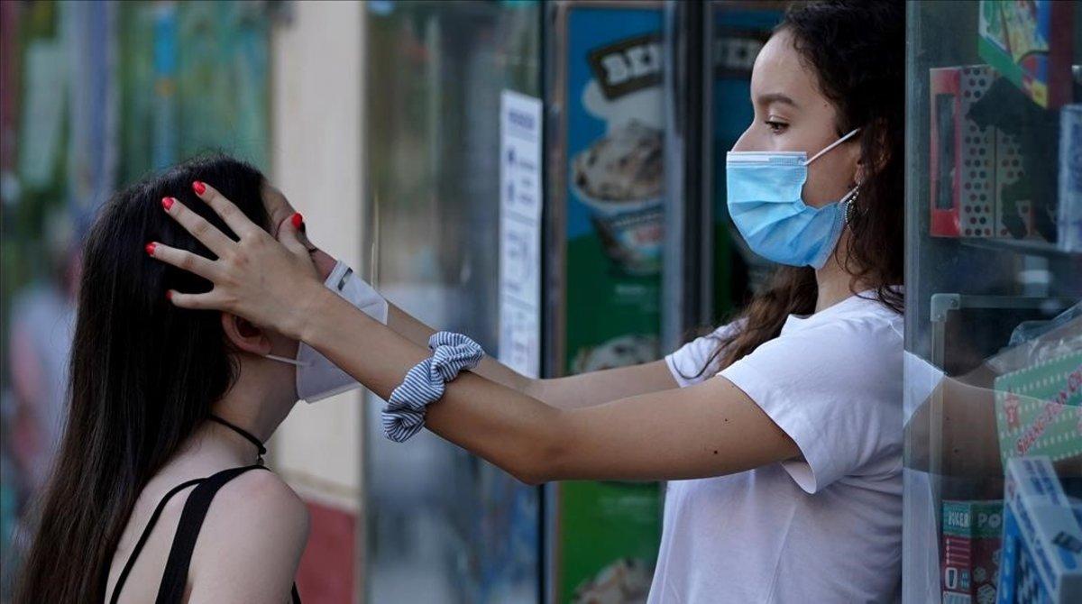 Una adolescente pone la mascarilla correctamente a una amiga, en Madrid.
