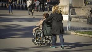 Una mujer acompaña a otra en silla de ruedas en Barcelona.