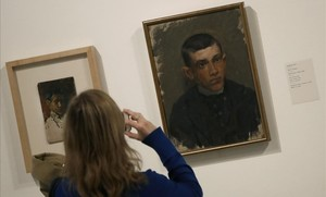 Una mujer observa en el Museo Picasso un Autorretrato del pintor malagueño de 1896 y un Pablo Picasso de Ramon Riu.