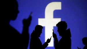 Usuarios consultan sumóvil delante de una pantalla en la que se proyecta el logo de Facebook