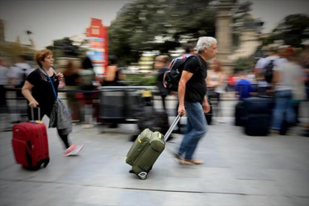 Viajeros 8Una pareja con sus maletas y mochilas, ayer en una calle de Barcelona.