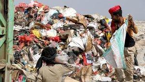 Dos yemenís buscan comida en un vertedero en la ciudad de Aden, Yemen.