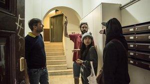 Los vecinos Schmid, Maestri y Mi Purk tratan de disuadir a un yonqui (de espaldas) en el vestíbulo de Peu de la Crdeu 21 bis, el viernes.