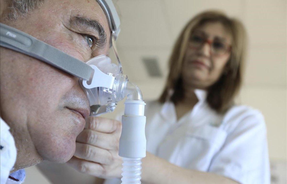 Conchi Ruiz, enfermera del equipo de especialistas en problemas del sueño del Hospital Clínic, con uno de sus pacientes.