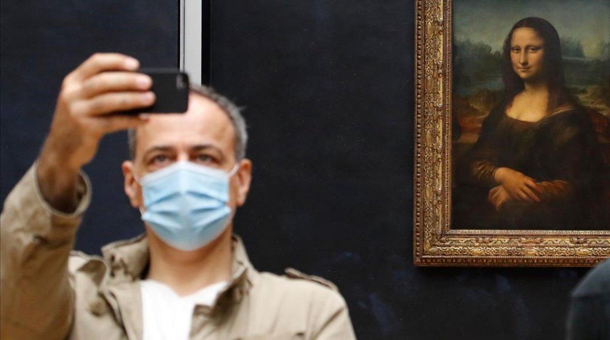 Un visitante se hace un selfi ante la Giocondaen el Louvre, inusualmente despoblado, la semana pasada.