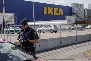 Un agent parla amb uns clients als afores de lIkea de Vasteras, a Suècia.