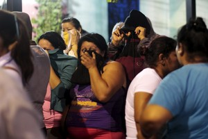Relatives wait for news outside a prison where 14 members of the Barrio 18 group were killed in Quezaltepeque