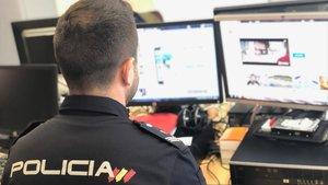 Un agente de Policía, frente a un ordenador con imágenes de pornografía infantil.