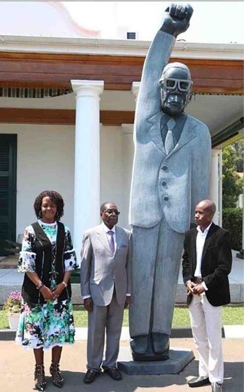 El artista Benhura (a la derecha), posa con el presidente Mugabe y su esposa Grace junto a la polémica estatua.