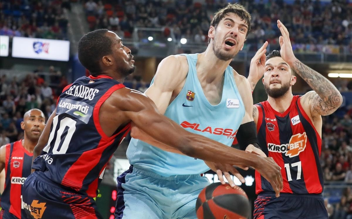 El azulgrana Tomic pugna con el pívot del Baskonia Poirier y el base Beaubois en una acción del partido