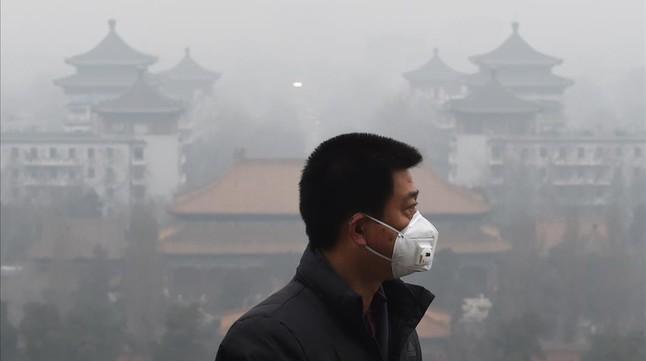 Un hombre protegido con una máscara, en las calles de Pekín