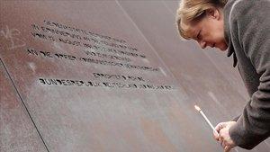 La canciller alemana coloca una vela en el Memorial del Muro de Berlín.