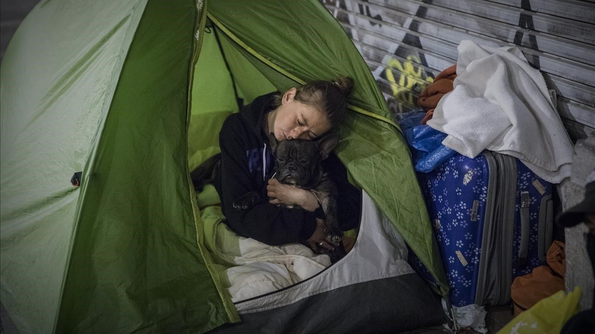 Una mujer acurruca a su perroen una tienda de campaña en los soportales del paseo de Picasso, este invierno.