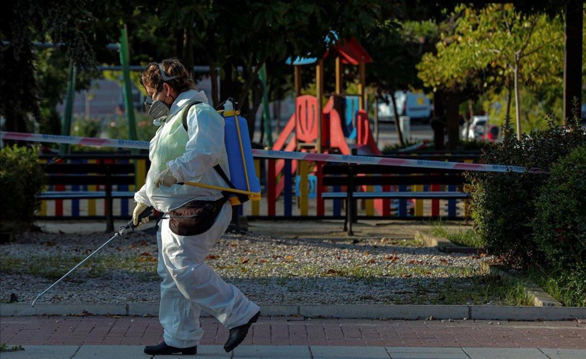 Una trabajadora municipal desinfecta los alrededores de un parque infantil en la localidad madrileña de Alcobendas.