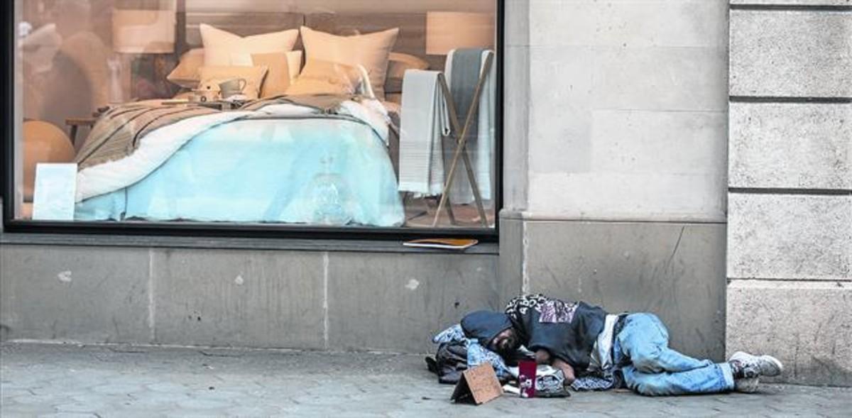 Un sintecho duerme junto al escaparate de una tienda de ropa de hogar, en el paseo de Gràcia.
