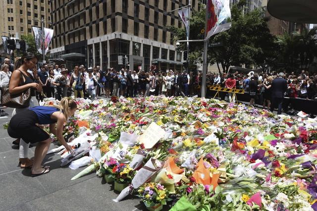 Cientos de ciudadanos se han acercado hasta el café, en el centro de Sidney, donde tuvieron lugar los hechos, para depositar ramos de flores y mensajes de condolencia