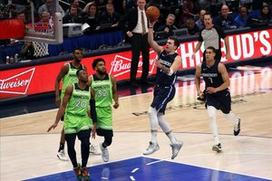 Doncic entra a canasta ante la mirada de tres defensores de los Timberwolves.