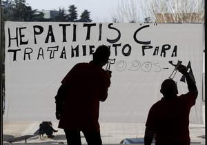 Dos hombres pintan un cartel reclamando acceso universal al nuevo tratamiento de la hepatitis C, en Navarra.