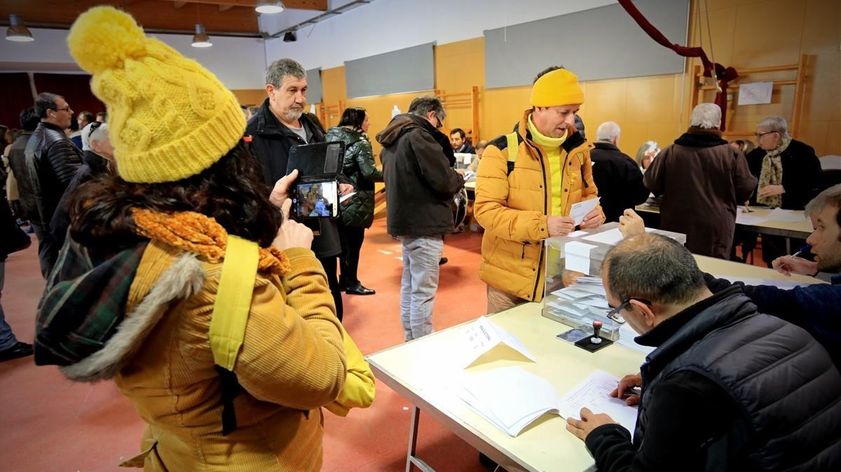 Dos personas acuden vestidas de amarillo a votar en el colegioelectoral La Llacuna del Poblenou.