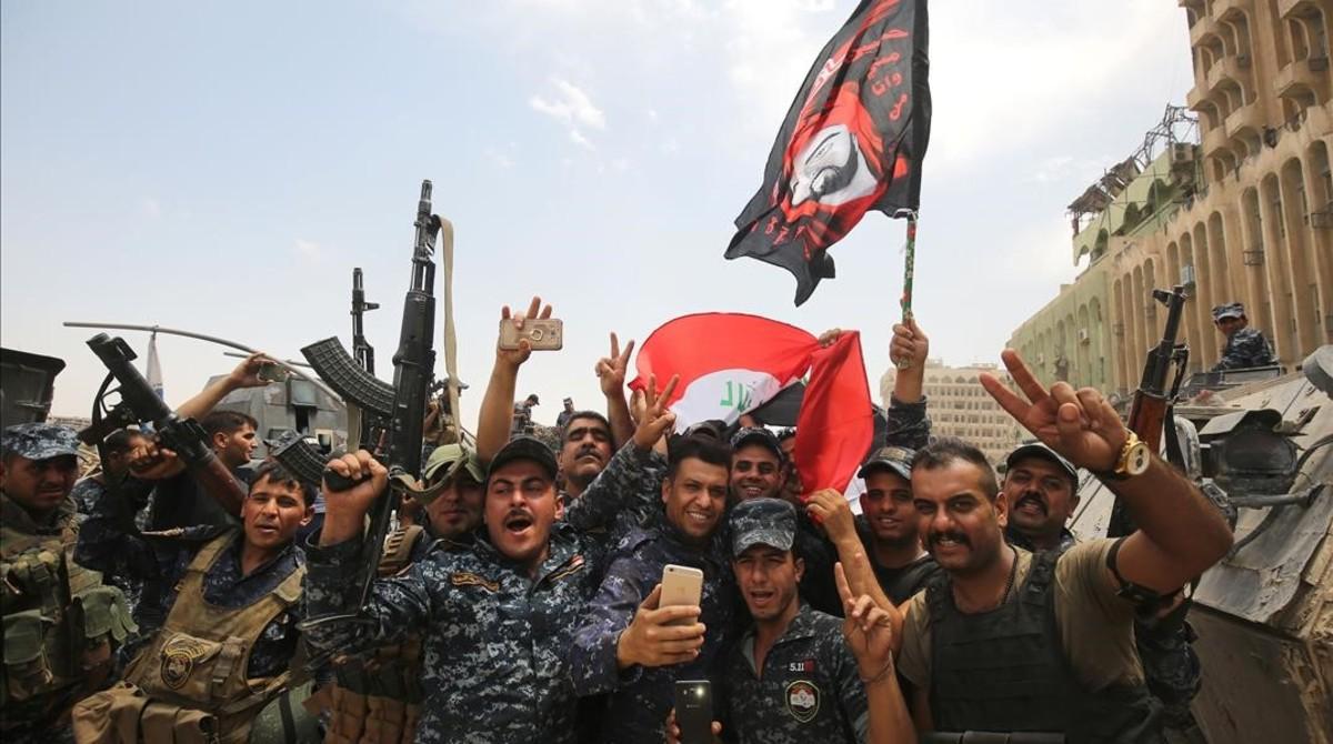 Soldados del Ejército iraquí celebran la reconquista deMosul.